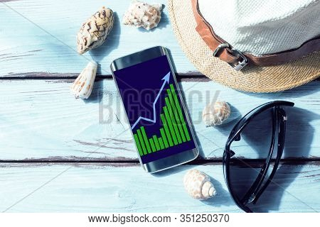 A Smartphone With A Financial Schedule, A Beach Towel, Sunglasses And Shells. Business Chart. Freela