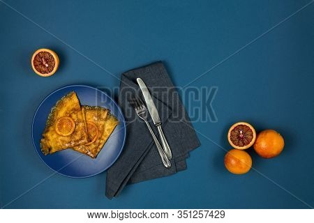 Two Crepe Suzette Pancakes Golden Toasted With Slices Of Red Orange And In Syrup On A Plate With Cut