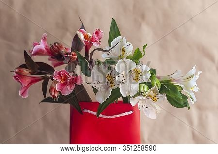 Flower Shop. Giving Flowers. Hands Holding Spring Flowers Bouquet Against The Crafty Paper Backgroun