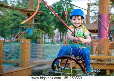 Little Cute Boy Enjoying Activity In A Climbing Adventure Park On A Summer Sunny Day. Toddler Climbi