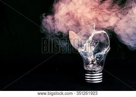 One Broken Light Bulb On A Black  Background With Smoke. Overdue Idea Concept. World Not Electric. E