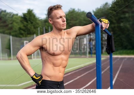 A Muscular Man Stands Near Parallel Bars, With A Bare Torso.