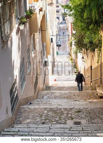 Old Man Hold Handrail And Slowly Walks Down By Rough Stony Stairs In Old Town. Historical Centre Of