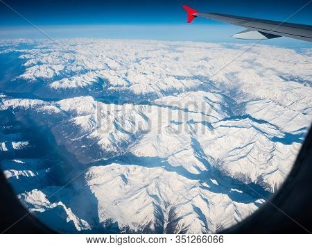 Plane Window Screen, Airbus Wing With Red Winglet, Sharp Peaks Of Snowy Winter Mountains Bellow In D