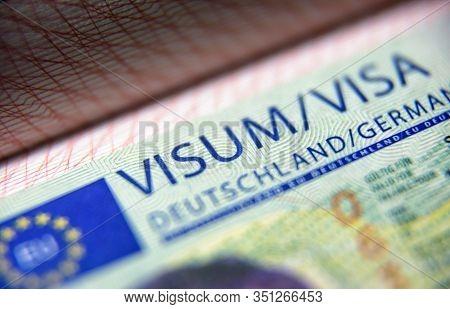 Visa Stamp In Passport Close-up. German Visitor Visa At Border Control. Macro View Of Schengen Visa