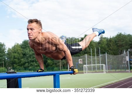 A Muscular Man Is Wrung Out From Parallel Bars.