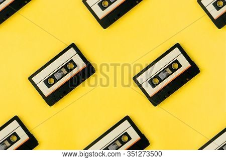 Seamless Pattern With Audio Cassettes Flat Lay On Colorful Yellow Background Top View. Creative Fash