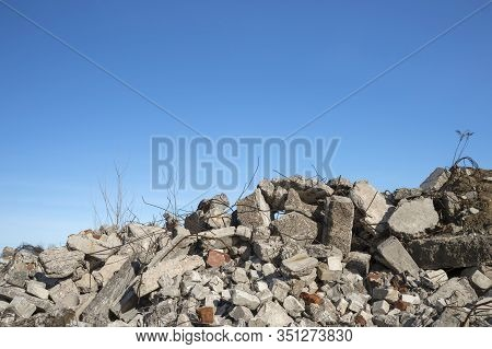 A Pile Of Large Gray Concrete Fragments With Protruding Fittings Against A Blue Cloudy Sky. Backgrou