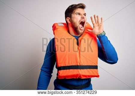 Young blond tourist man with beard and blue eyes wearing lifejacket over white background shouting and screaming loud to side with hand on mouth. Communication concept.