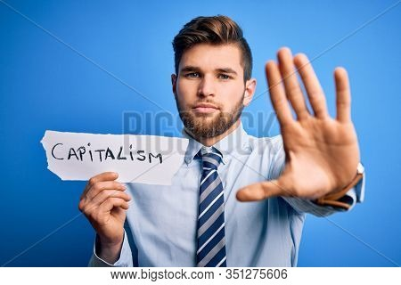 Young blond businessman with beard and blue eyes holding paper with capitalism message with open hand doing stop sign with serious and confident expression, defense gesture