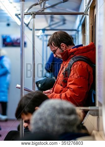 Moscow, Russia - February 8, 2020: Man Rides In Subway Car And Reads A Magazine. Guy With Glasses An