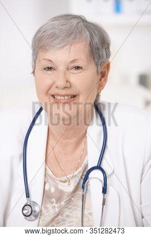 Portrait of senior female doctor, wearing white coat and stethoscope, smiling.
