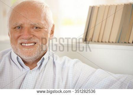 Closeup portrait of happy pensioner smiling at camera.