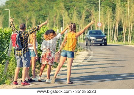 Mixed Race Group Of Best Friends Hitchhiking On The Side Of Countryside Road During Great Summer Adv