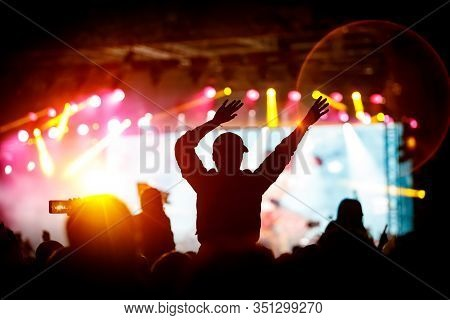 The Crowd With Their Hands Up Enjoys Music Concert. Fan Silhouette On Stage Background.