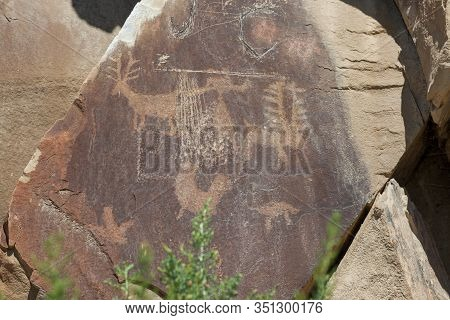 Ancient Petroglyphs Of Animals And A Man Like Figure Are Carved Into Sandstone Rocks Along With Some