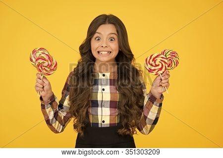 Always Eat Dessert First. Happy Small Schoolchild Hold Candy Dessert On Sticks. Little Girl Smile Wi