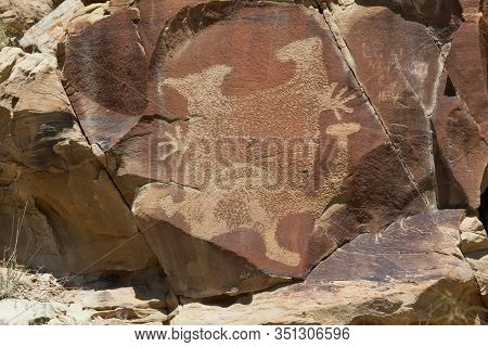 An Ancient Petroglyphs Of A Strange Creature On A Sandstone Rock With More Modern Graffiti From 1834