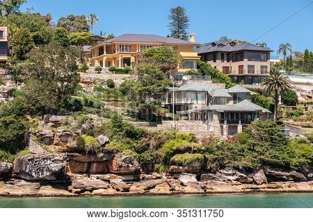 Sydney, Australia - December 11, 2009: Upscale Housing With Gray Roofs On Rocky Slope With Green Veg