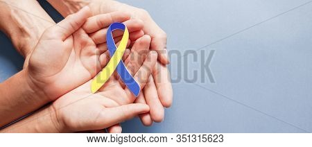 Adult And Child Hands Holding Blue And Yellow Ribbon Shaped Paper, Down Syndrome Awareness , World D