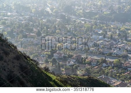 Hazy mountaintop view of suburban streets and homes in the Granada Hills neighborhood of Los Angeles, California.