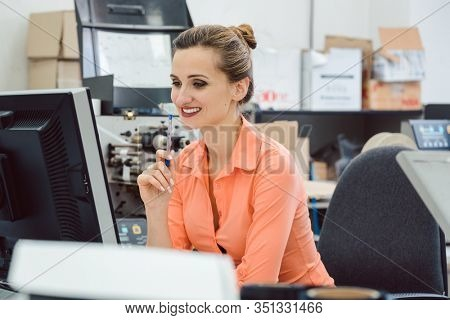 Woman designing labels to be printed on label printer in workshop looking at computer screen