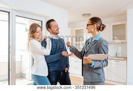 Cheerful realtor giving house key to the buyers or tenants