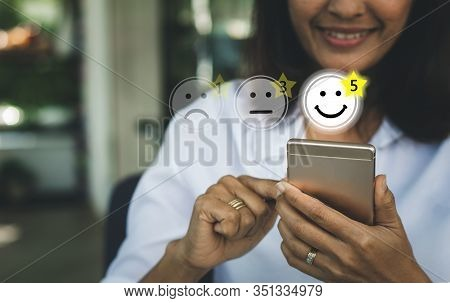 Businesswoman Pressing Face Emoticon On Virtual Touch Screen At Smartphone .customer Service Evaluat