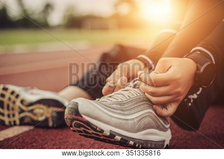 Mature Fitness Woman Tie Shoelaces On Road. Cheerful Runner Sitting On Floor On City Streets With Mo