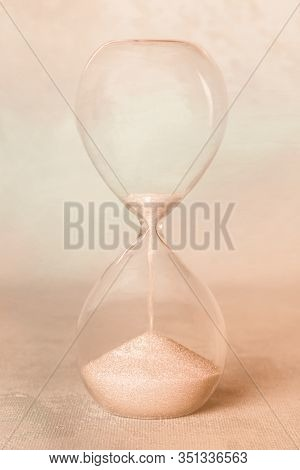 Time Concept. An Hourglass On An Abstract Background. Sepia Toned Image