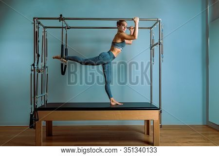 A Young Girl Does Pilates Exercises With A Bed Reformer, Barrel Machine Tool. Beautiful Slim Fitness