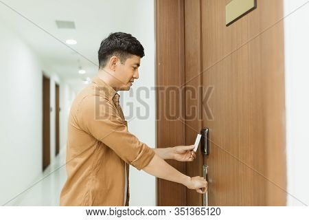 Asian Man Hand Holding Access Card / Key Card Eletronic Door Accessing Control Scanning To Lock And