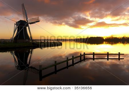 Windmill at a lake with sunset sky