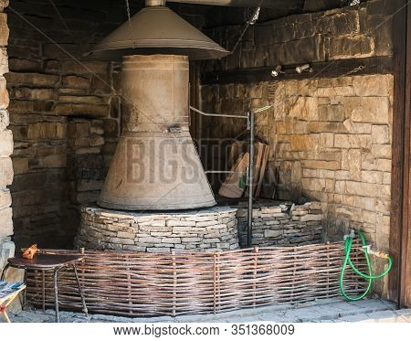 Reconstruction Of Old Metal And Stone Stove. Exposition At The Walls Of The Genoese Fortress