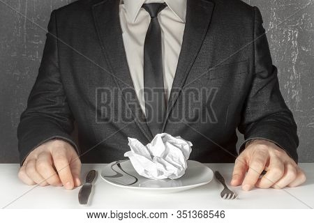 A Man Without A Face In A Black Suit And Tie Sits At A Table And Prepares To Eat A Crumpled Sheet Of