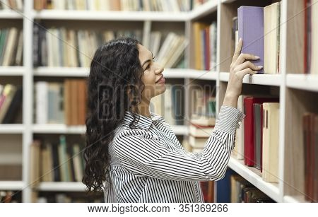Young Librarian. Smiling Mexican Girl Taking Book From Library Bookshelf, Searching And Choosing Man