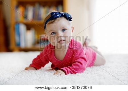 Baby Girl With Blue Eyes Lying On Belly. Nursery For Children. Textile And Bedding For Kids. Happy C