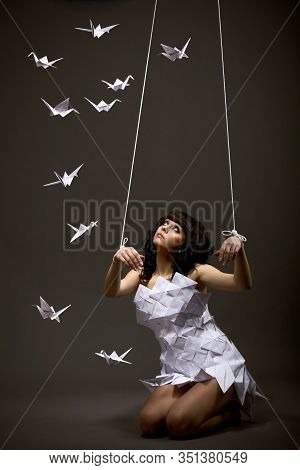 Sad Beautiful Young Caucasian Girl In Origami Dress Looks Up With Hands Tied Up Like A Puppet Next T