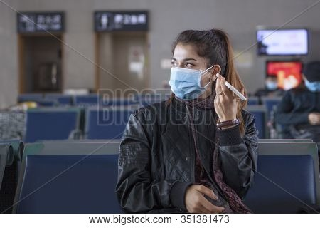The Girl Is Sitting At The Airport Leaving China. Listens To Voice Messages On The Phone. Medical Ma