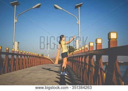 Sproty Woman Taking Picture With Cell Phone On The Bridge.