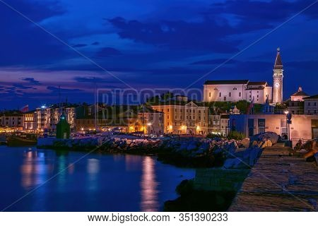 Picturesque Nightscape Of Coastline Of Adriatic Sea With Illuminated Houses And Lighthouse At Twilig