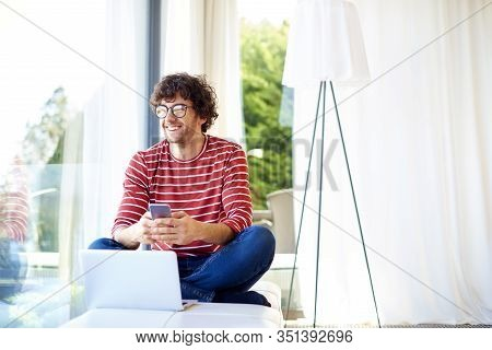 Happy Young Man Daydreaming And Text Messaging While Sitting At Home