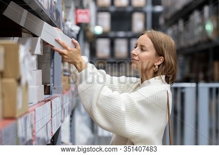 Female Customer In White Sweater Picks Up Goods In Self-service Warehouse, Side View. Shopping Conce