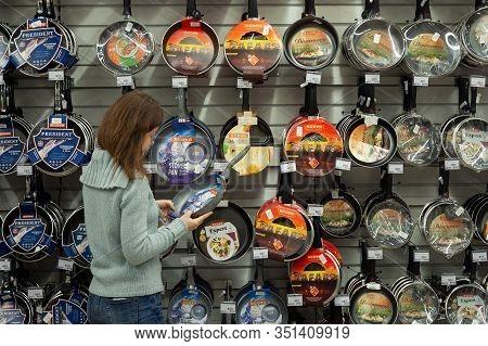 Minsk, Belarus - January 29, 2020: Woman Choosing Frying Pan In A Supermarket. Large Selection Of Pa