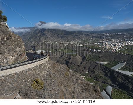 View On Car At Curved Winding Asphalt Road In Steep Rocky Mountain Slope With Subtropical Volcanic L