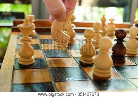 Men Hand Hold And Moving Chess Horse On The Board To Compete With Opponent. Strategic Planning Board