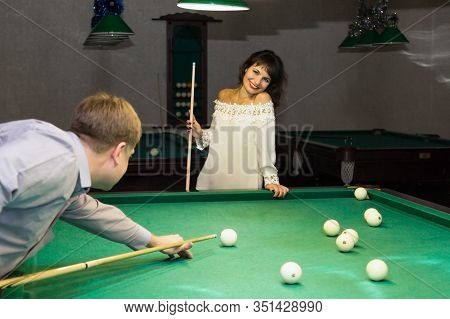 Adult Man And Woman Play Billiards. A Man Of 40 Years Old And A Brunette Woman Of 30-35 Years Old Ne