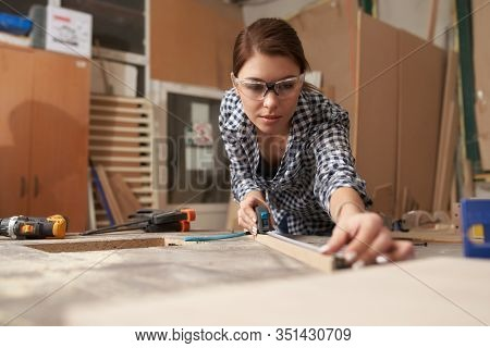 Young woman woodworker with wooden board behind workbench