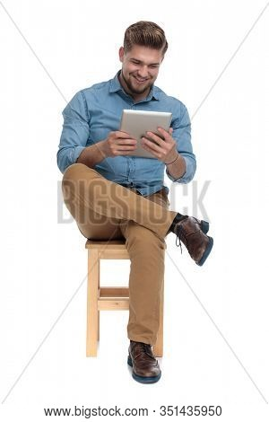 hapy young man in denim shirt smiling and holding tab, sitting isolated on white background, full body