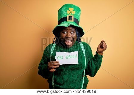 Plus size african american woman wearing green hat holding paper on saint patricks day screaming proud and celebrating victory and success very excited, cheering emotion